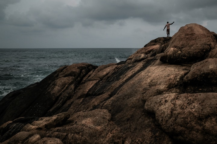 A man throws a stone into the ocean on a rocky outcropping in Sri Lanka - Pics Of Asia Photo Tours