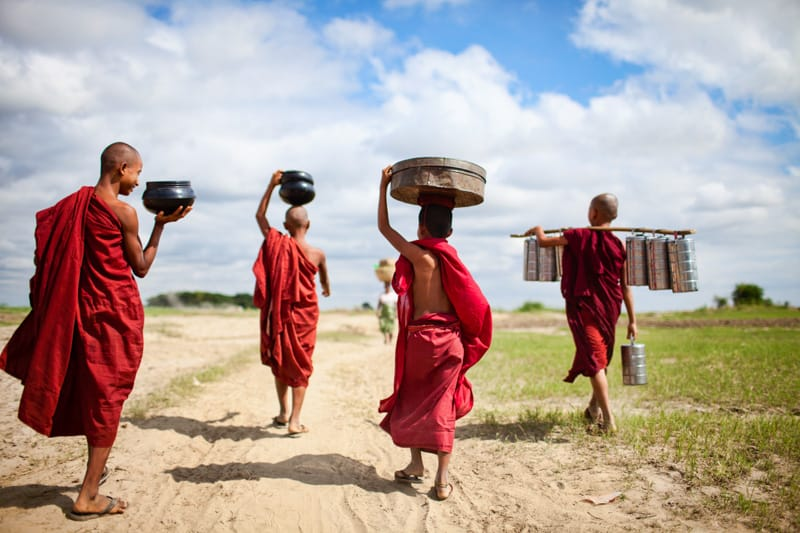 Young monks collect water and walk down a dirt path in red robes, Burma, Myanmar, Bagan - Pics Of Asia Phototours