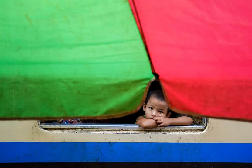 Burmese girl siting on the train behind a green and red umbrella during a Pics of Asia photography tour in Myanmar