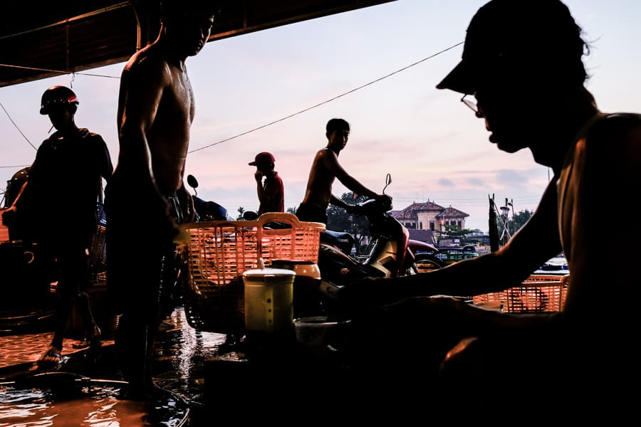 men selling fish in the wet market of Sa Dec in the Mekong delta