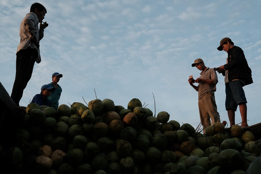 men standing on top of coconuts in Lonh Xuyen floating market in South Vietnam