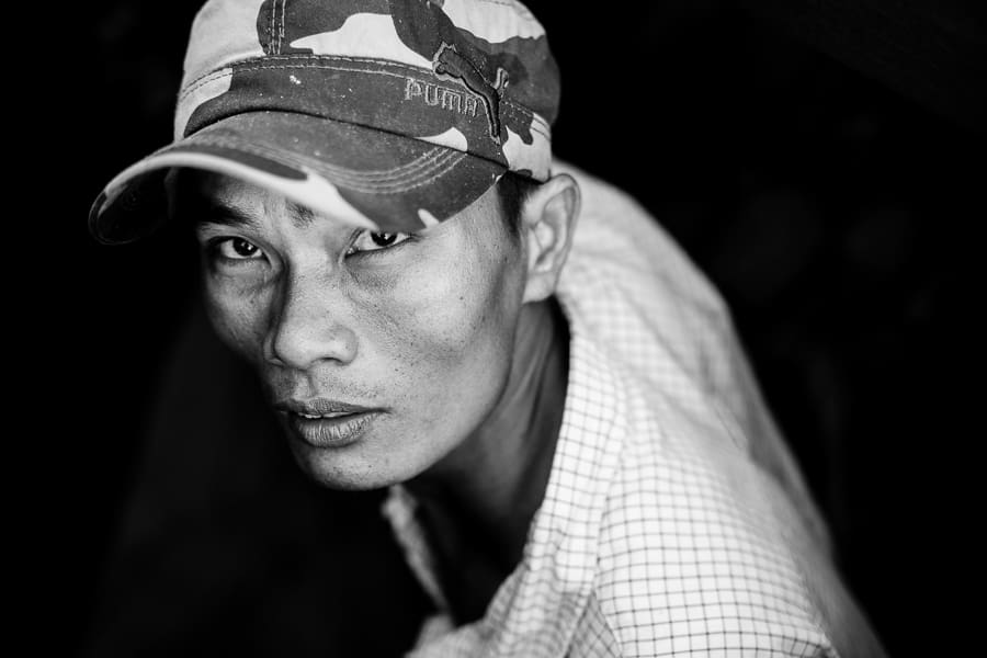 Black and white portrait of a man looking up in Vietnam's Mekong Delta