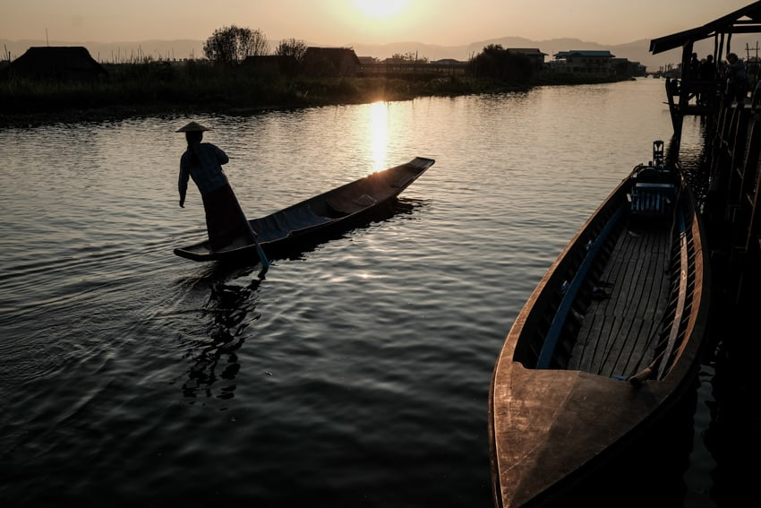 Woman rowing her boat at sunset on Inle lake, Myanmar