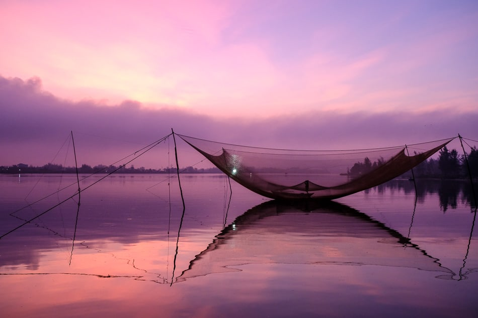 Fisherman attending his net on the river in Vietnam