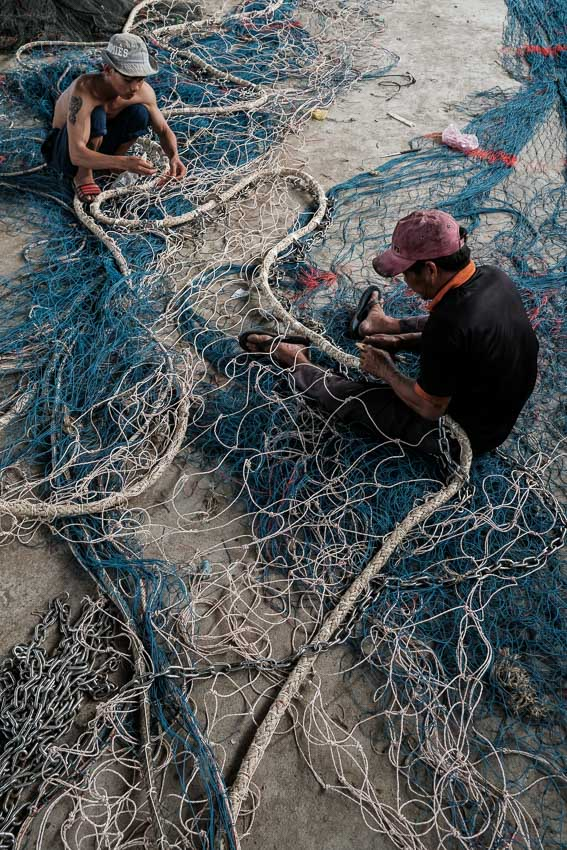 two fishermen working on a big fishing net in the village of Sa Huynh in central Vietnam during a Pics of Asia photography tour