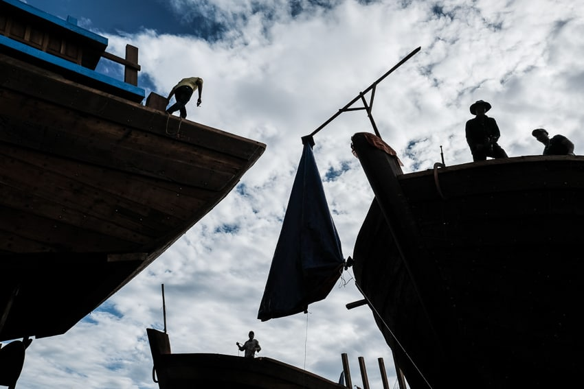 silhouette photo of wood workers working on fishing boats in a shipyard of central Vietnam
