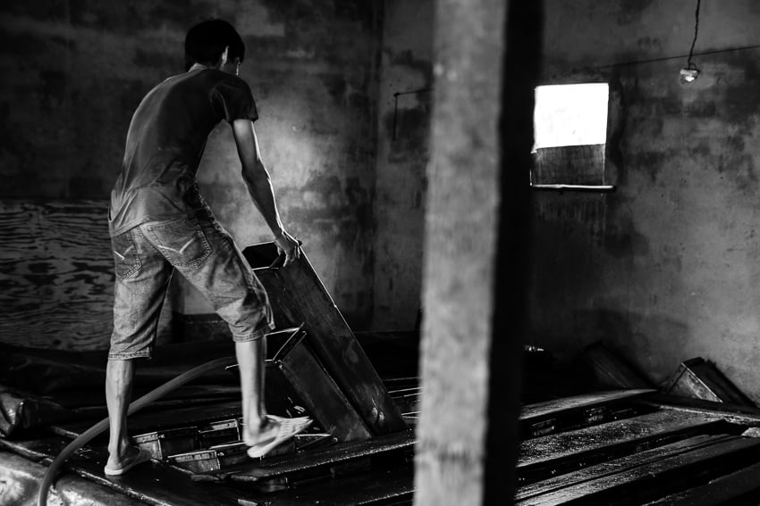 black and white image of a man working in an ice factory in a fishing village around Hoi An during Pics of Asia photo tour
