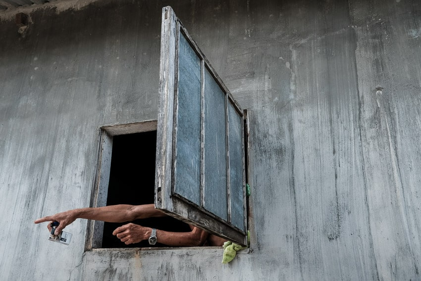 A man points out of his window in a fishing village in central Vietnam during Pics of Asia photography tour