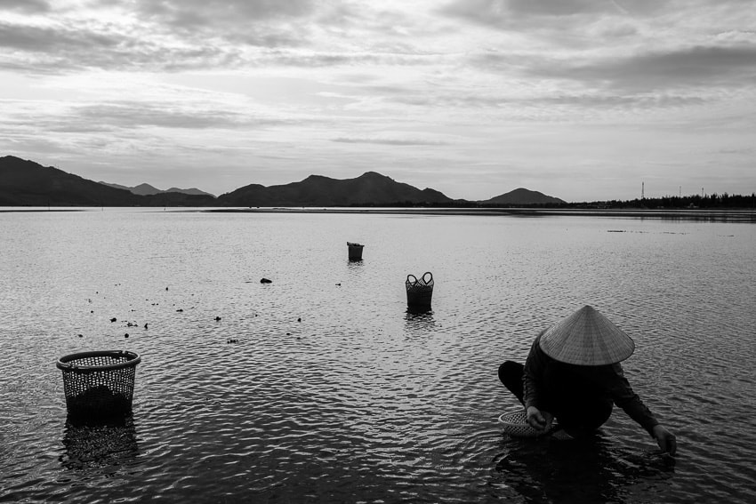 Playing with lines for a composition of a woman harvesting oysters in the water of Lang Co lagoon in central Vietnam during Pics of Asia photography tour