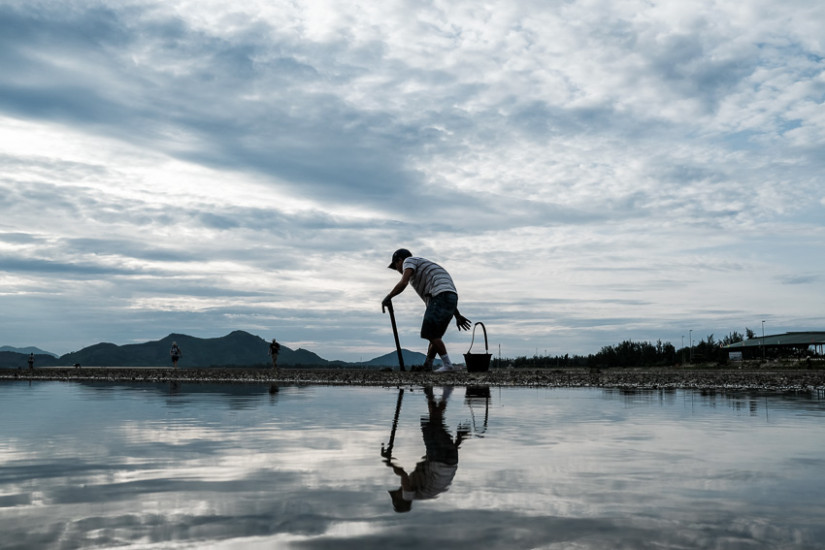 Vietnamese man looking for works in ang Co lagoon mud during a photography tour with Pics of Asia