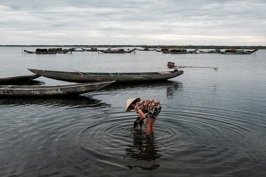 A Vietnamese woman cleaning a fishing net in the water of Tam Giang Lagoon during Pics of Asia photography workshop