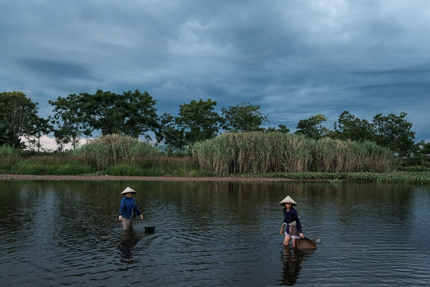 women harvesting clams in the river near Hoi An, taken on a photography workshop with Pics of Asia