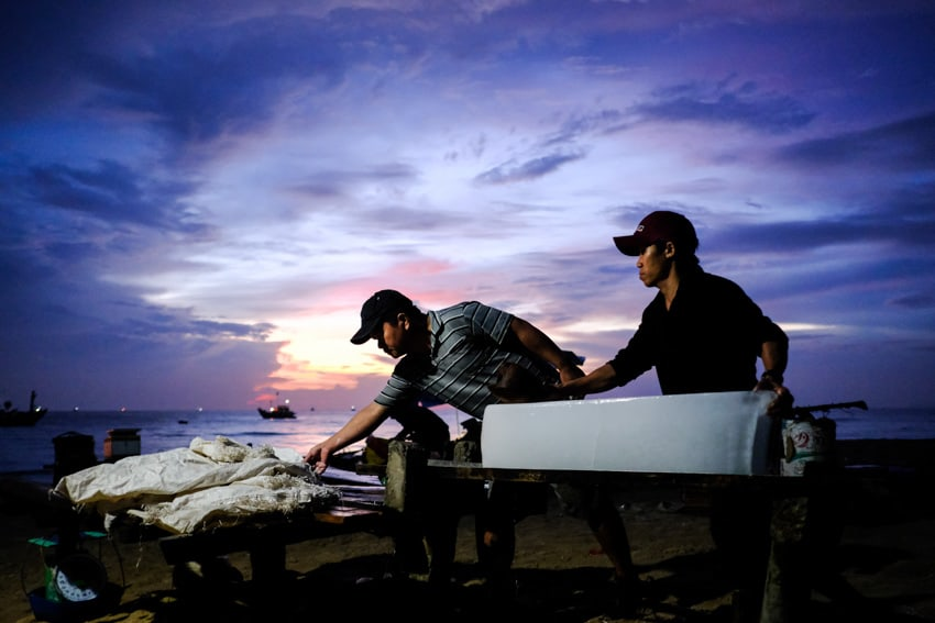 Two Vietnamese fishermen push ice at dawn near Hoi An