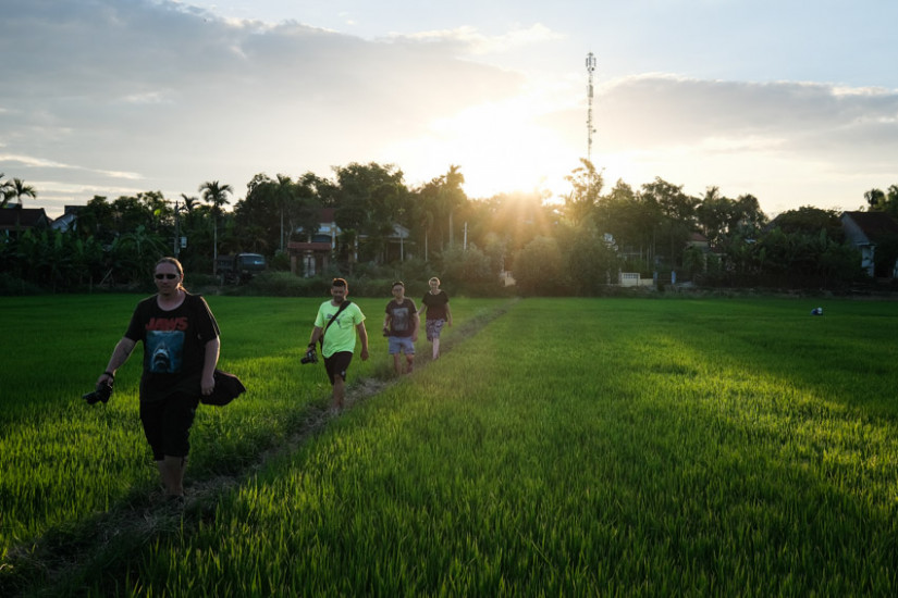 Pics of Asia photography tour group walking in the rice fields of hoi an at sunset