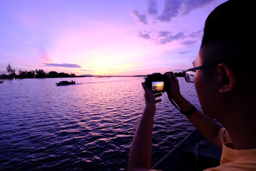 Student taking a photo of the sunrise in Hoi An on a photography tour with Pics of Asia
