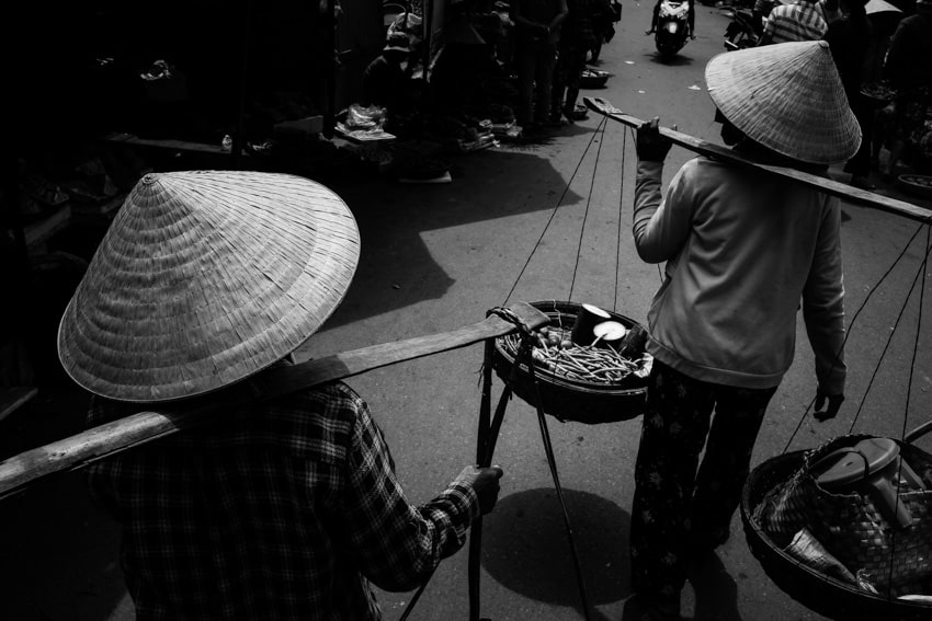in hoi an market in the morning 2 women are walking