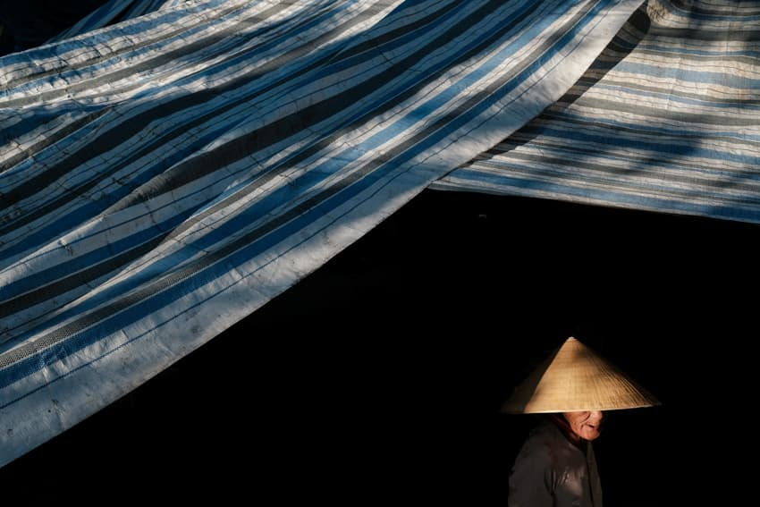 A woman with a conical hat walks in hoi an market, taken during a photo tour with Pics of Asia