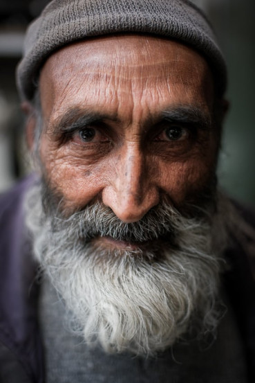 Close up portrait of an Afghani man in a shop in Yazd during Pics of Asia photography tour in Iran