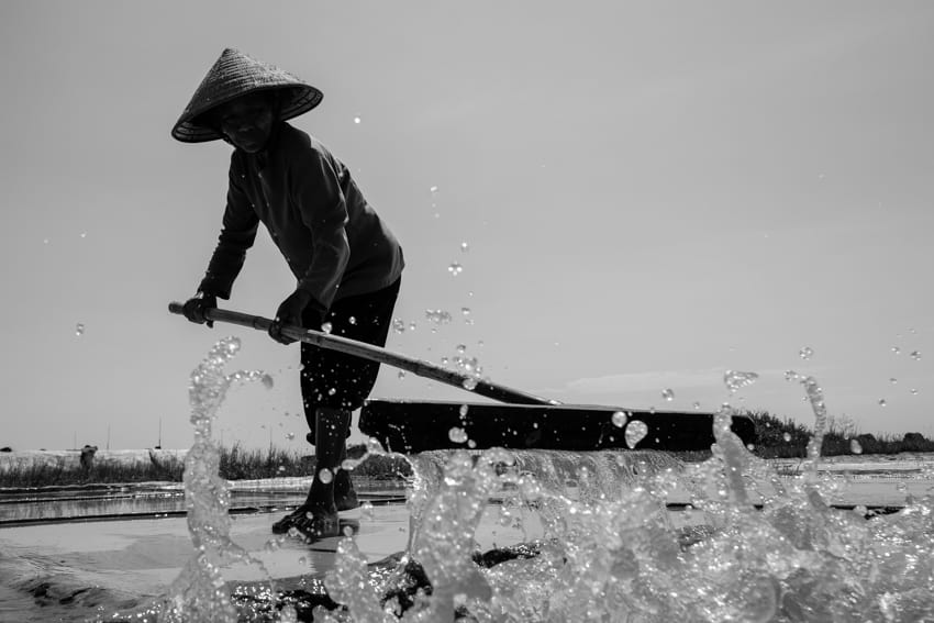 Nam Dinh salt farm worker, pushing water into pools, during a photography tour with Pics of Asia