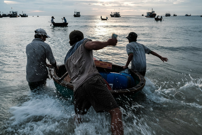 Fishermen unloading their fish on the beach at sunrise during a photography tour with Pics of Asia around Hoi An
