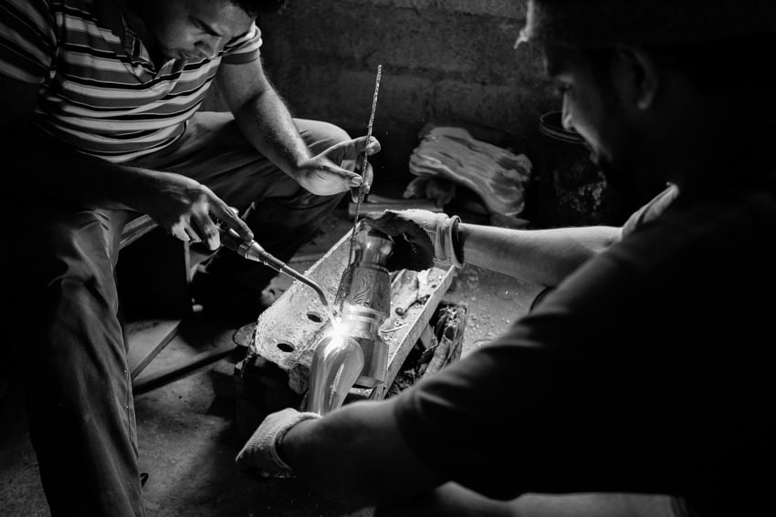 Two men welding a brass statue in the countryside of Kandy, Sri Lanka