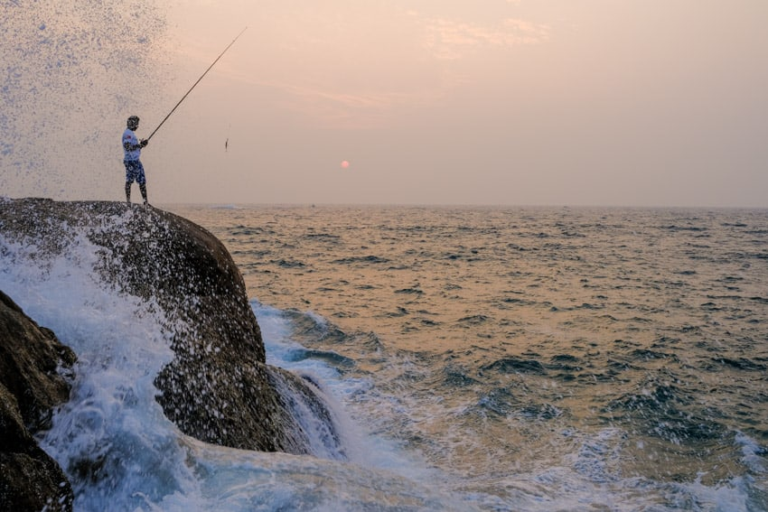 A man is fishing at sunset on a rocky cliff near Galle, Sri Lanka