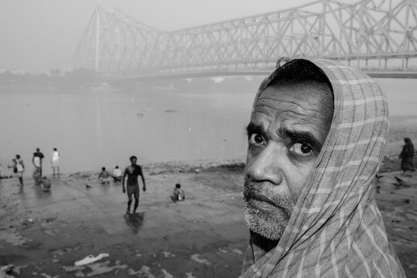 A man stares at the camera in front of the Howrah bridge, Kolkata