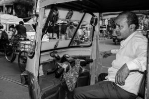 an auto rickshaw driver waits for a ride in the streets of Kolkata, India
