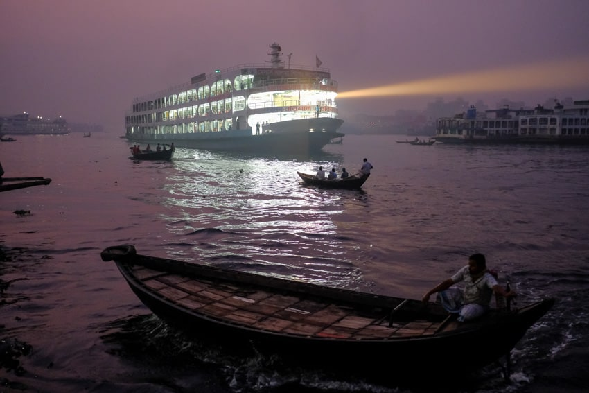 Boats commuting on the Buriganga river at sunrise in Dhaka, Bangladesh