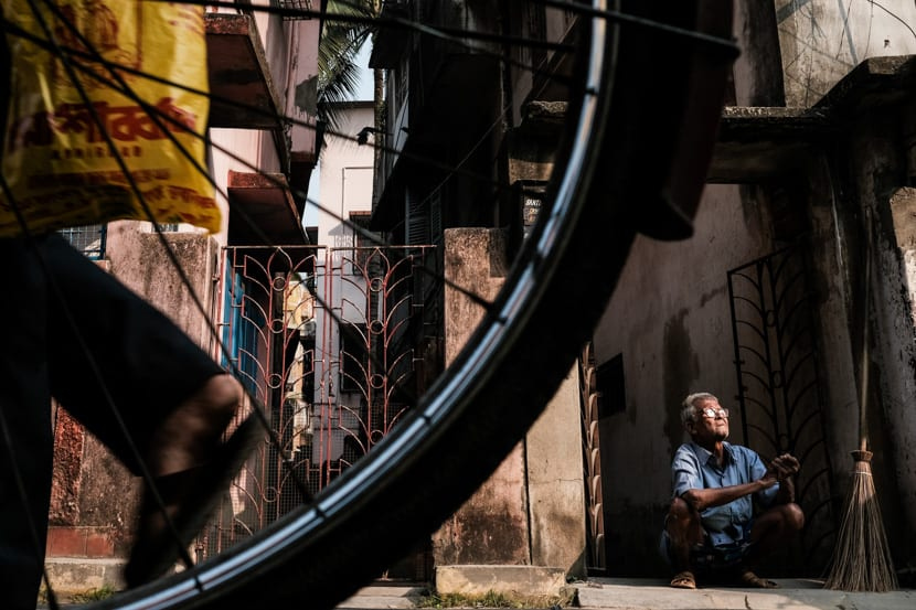 A man sitting in a street of Kolkata captured through a bicycle wheel during a photography tour with Pics of Asia