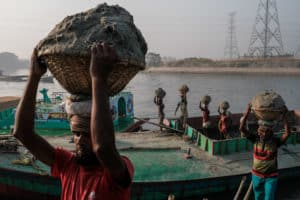 Lines of workers unload sand, rocks and coal from boats along he river in Dhaka, during a photography tour with Pics of Asia