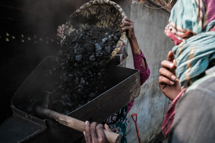 Workers grinding coal through a machine in a brick factory in the surroundings of Dhaka