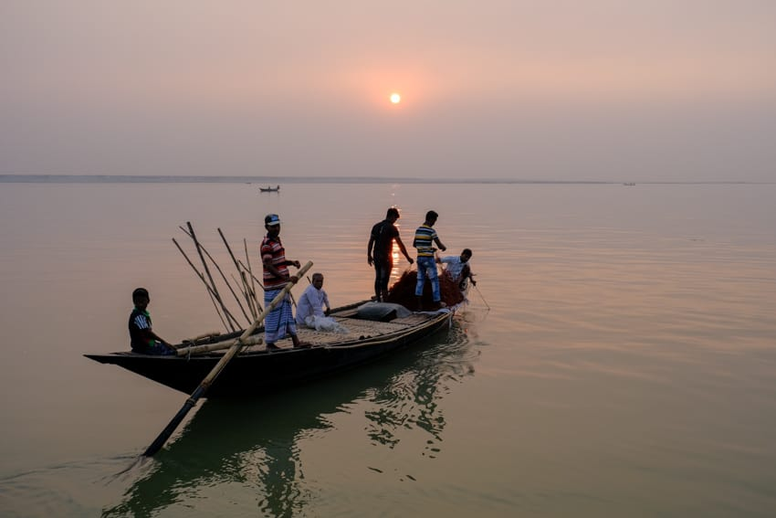 A group of fishermen leading their nets back on a boat at sunset on the Padma river, Bangladesh