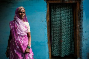 A woman dressed in a purple sari poses in front of her blue house in the countryide of Varanasi during a photography tour with Pics of Asia