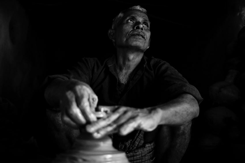 An Indian man sitting in his workshop doing clay pots during a photography tour with Pics of Asia