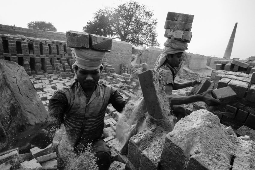 Two men carrying bricks in a brick factory near Varanasi, India