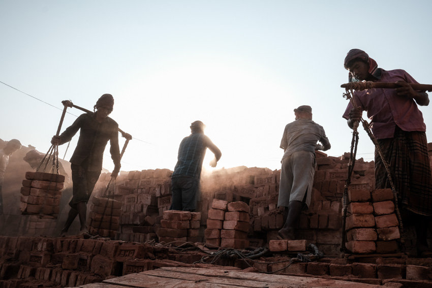 Four men unloading bricks from a factory near Dinajpur in Bangladesh during a photography tour with Pics of Asia