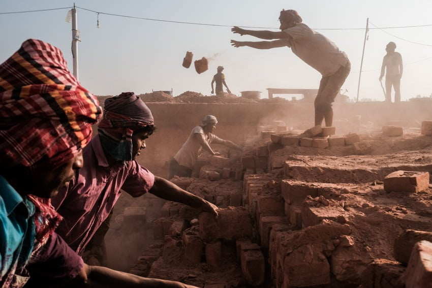 Workers of a brick factory in bangladesh sorting out old and new bricks