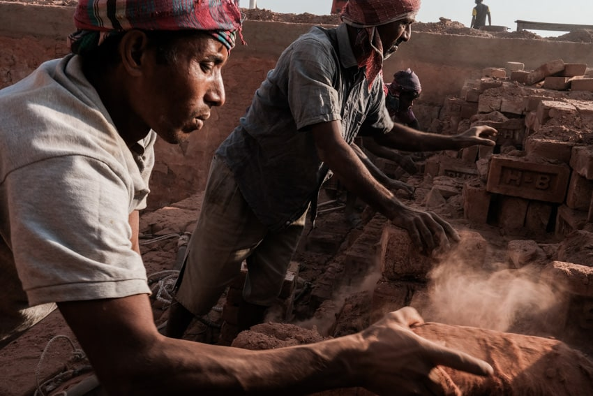 Two men working in a brick factory in Bangladesh early morning