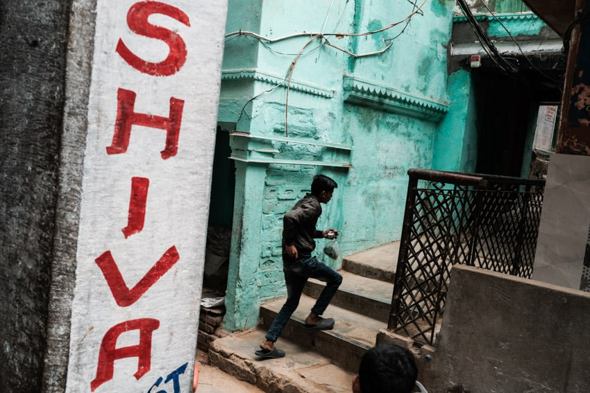 A man walks in the streets of Varanasi with a Shiva sign in the foreground
