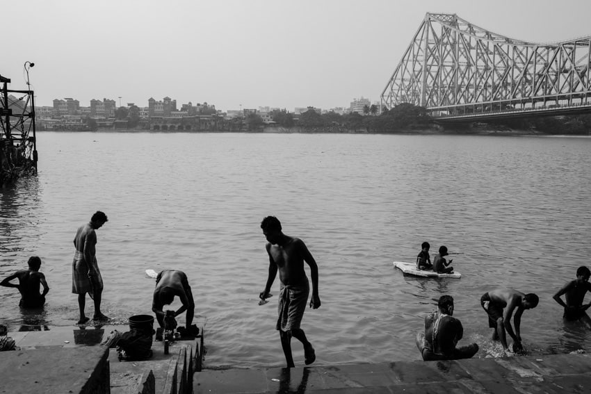 People take a spiritual bath in the water of the Ganges in Kolkata, India