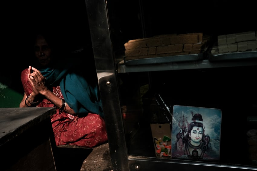 Street photo of an India woman joining her hands next to an image of Shiva in Varanasi, during a photography tour with Pics of Asia
