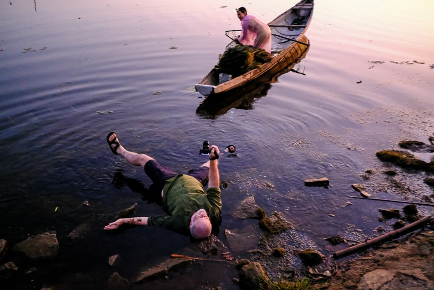 A particcipant of Pics of Asia photography tour taking photos laying down in the water in Vietnam