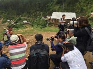 a group of photographers on a photography tour taking photos of a staged scene, used to illustrate an article about ethics in travel photography for Pics of Asia