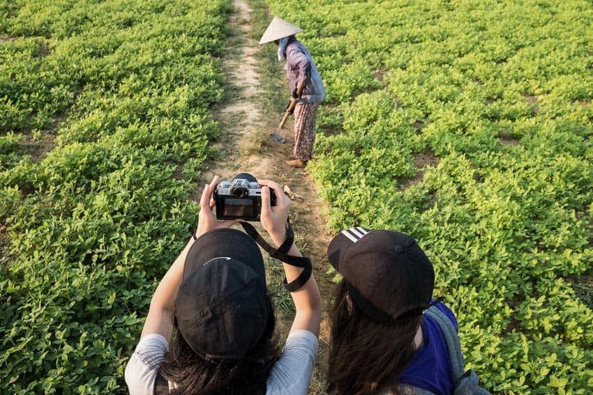 students from international school taking photos of farmers in the fields outside of Hoi An during a photography tour with Pics of Asia