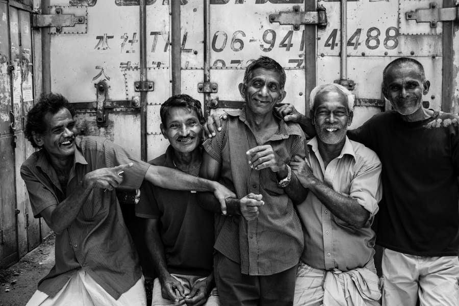 A group of friendly men posing for a photo in Negombo market on a photography tour with Pics of Asia in Sri Lanka