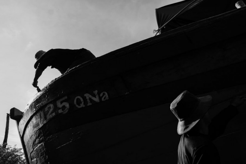 Two men painting a fishing boat in a shipyard in central Vietnam