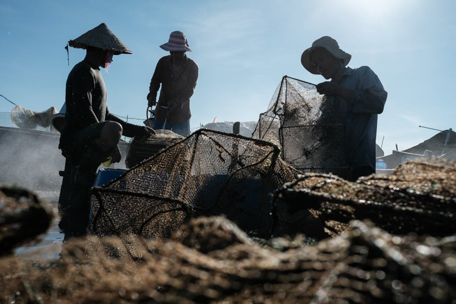 Fishermen cleaning their nets in a lagoon in Hue for a contact sheet for Pics of Asia