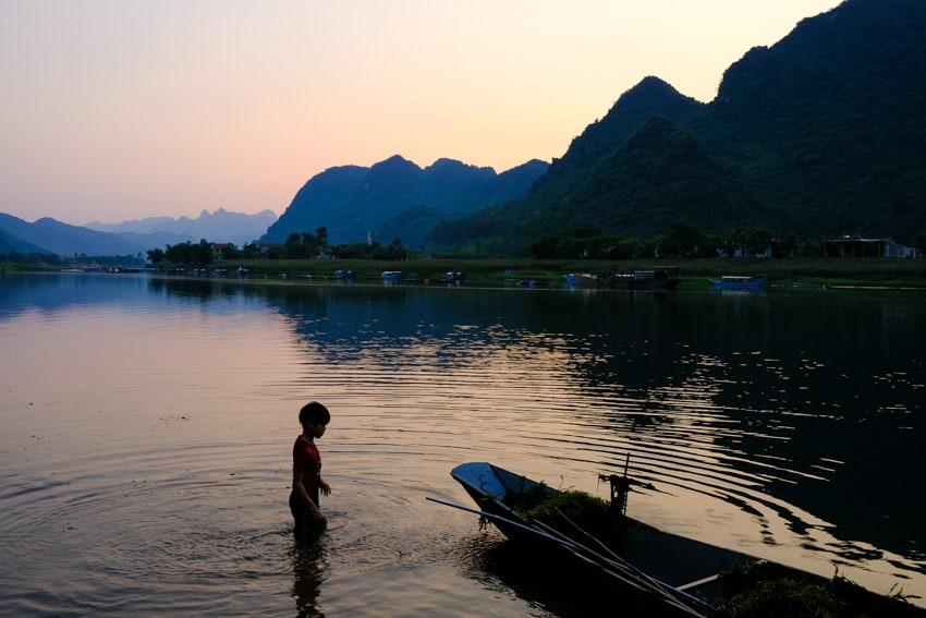 boy gathering weeds in the river in phong nha at sunset