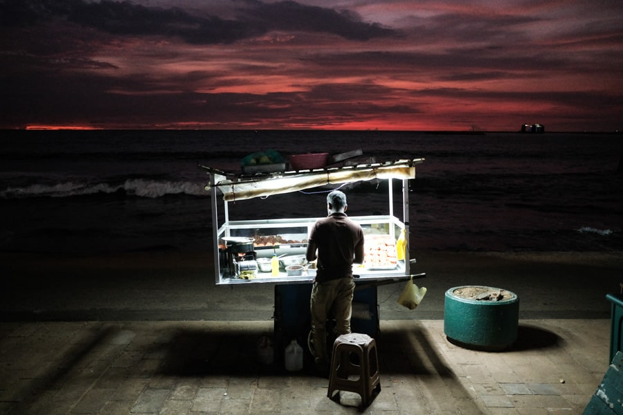A man selling street food at sunset on Galle face in Colombo